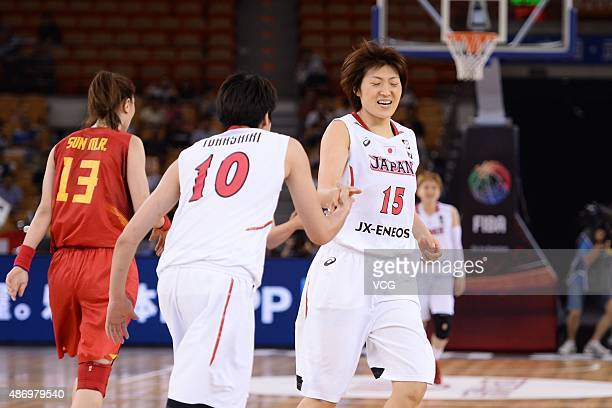 Ramu Tokashiki of Japan claps hands with and Asako O of Japan in finals match between Japan and China during the 2015 FIBA Asia Championship for...