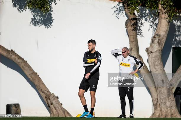 Ramy Bensebaini and Assistant Coach Oliver Neuville of Borussia Moenchengladbach are seen during the Borussia Moenchengladbach Training Camp on...