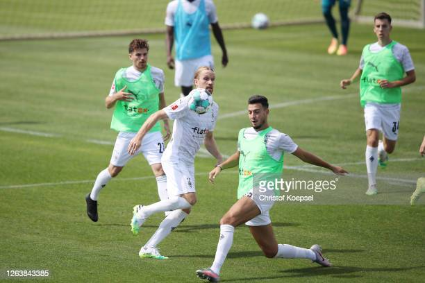 Ramy Bensebaini challenges Michael Lang attends the first training session after the summer break at Training Ground on August 04, 2020 in...