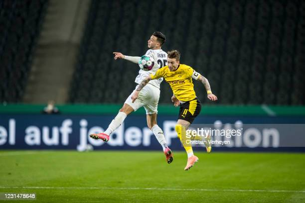 Ramy Bensebaini of Borussia Moenchengladbach and Marco Reus of Borussia Dortmund battle for the ball during the DFB Cup quarter-final match between...