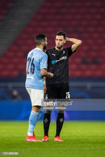 Ramy Bensebaini of Borussia Moenchengladbach and Riyad Mahrez of Manchester City are seen after the UEFA Champions League Round Of 16 Leg One match...