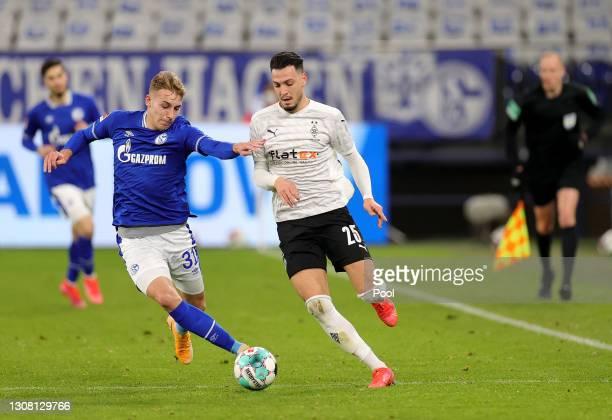 Ramy Bensebaini of Borussia Moenchengladbach and Timo Becker of FC Schalke 04 battle for the ball during the Bundesliga match between FC Schalke 04...