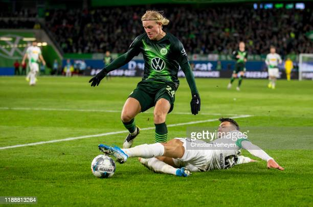Ramy Bensebaini of Borussia Moenchengladbach and Xaver Schlager of VfL Wolfsburg battle for the ball during the Bundesliga match between VfL...