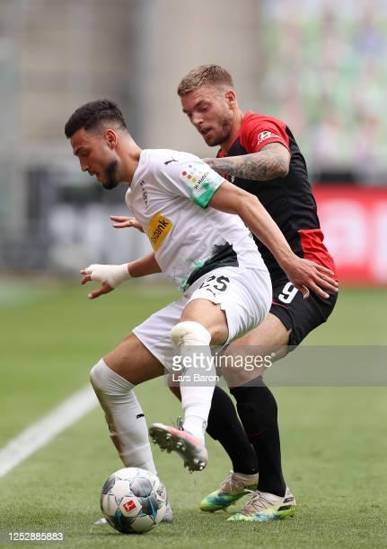 Ramy Bensebaini of Borussia Moenchengladbach battles for possession with Alexander Esswein of Hertha BSC during the Bundesliga match between Borussia...