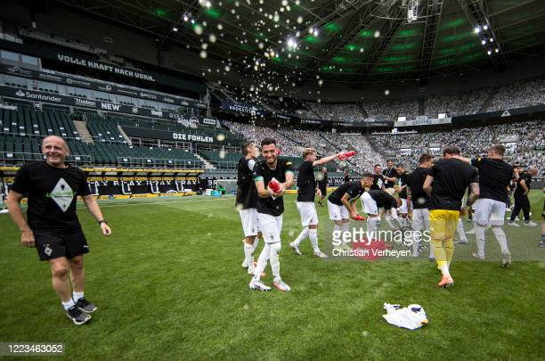 MOENCHENGLADBACH GERMANY JUNE Ramy Bensebaini of Borussia Moenchengladbach celebrate their win and Qualification for the Champions League after the...