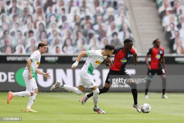 Ramy Bensebaini of Borussia Moenchengladbach holds of Dodi Lukebakio of Hertha BSC during the Bundesliga match between Borussia Moenchengladbach and...