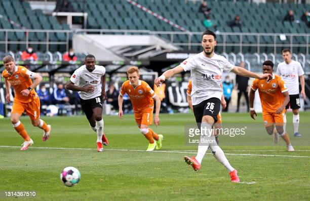 Ramy Bensebaini of Borussia Moenchengladbach scores their side's third goal from the penalty spot during the Bundesliga match between Borussia...