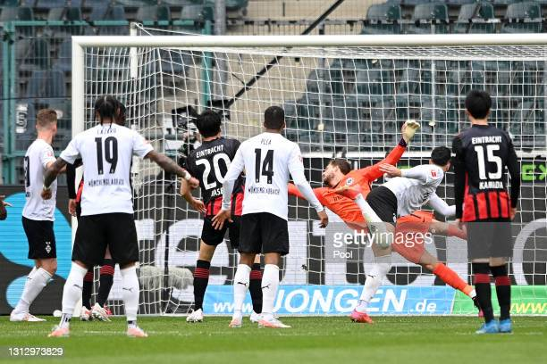Ramy Bensebaini of Borussia Moenchengladbach scores their team's third goal past Kevin Trapp of Eintracht Frankfurt during the Bundesliga match...