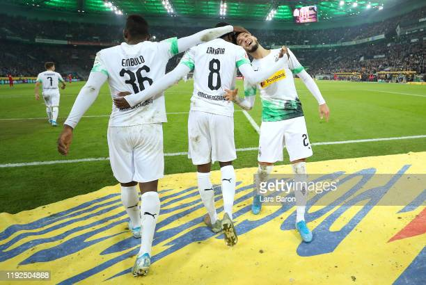 Ramy Bensebaini of Borussia Monchengladbach celebrates with Breel Embolo and Denis Zakaria after scoring his team's second goal during the Bundesliga...