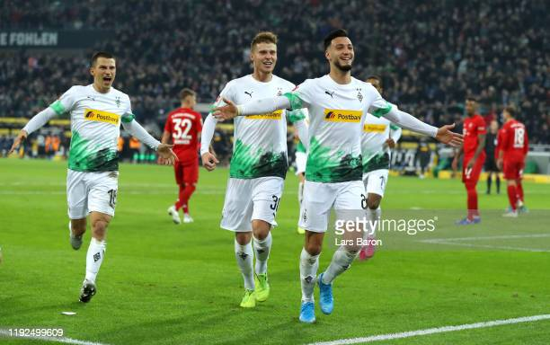 Ramy Bensebaini of Borussia Monchengladbach celebrates with Nico Elvedi and Stefan Lainer after scoring his team's first goal during the Bundesliga...