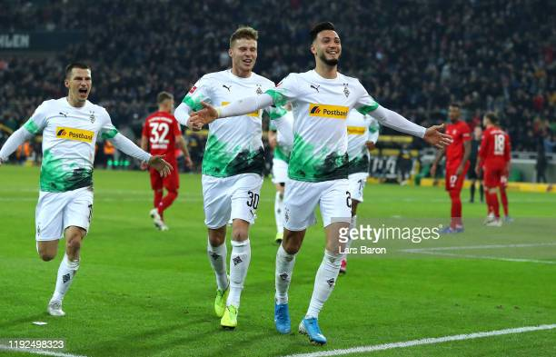 Ramy Bensebaini of Borussia Monchengladbach celebrates with Nico Elvedi after scoring his team's first goal during the Bundesliga match between...