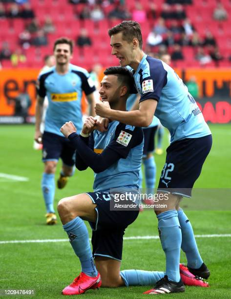 Ramy Bensebaini of Borussia Monchengladbach celebrates with teammate Florian Neuhaus after socring his sides first goal during the Bundesliga match...