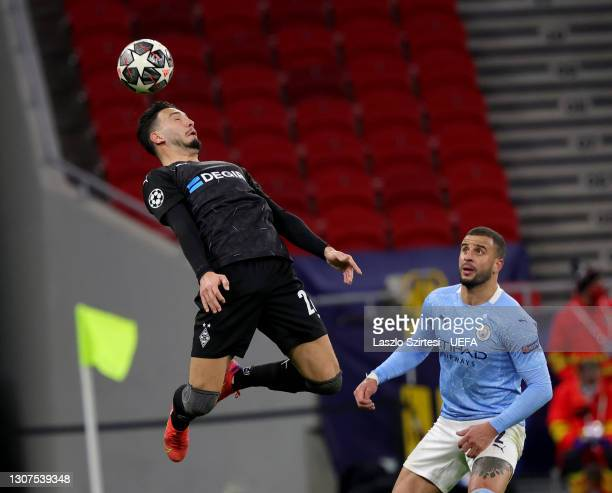 Ramy Bensebaini of Borussia Monchengladbach heads the ball next to Kyle Walker of Manchester City during the UEFA Champions League Round of 16 match...