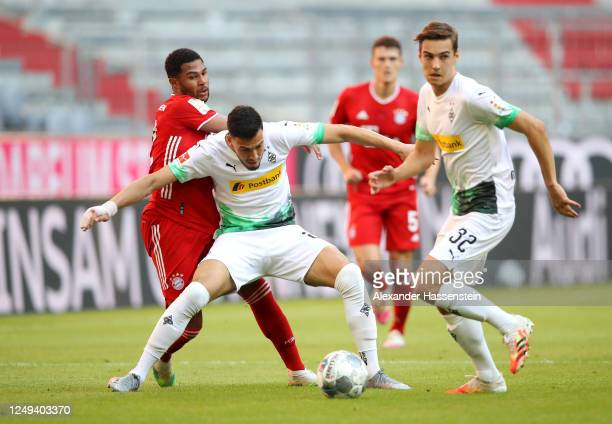Ramy Bensebaini of Borussia Monchengladbach is challenged by Serge Gnabry of Bayern Munich during the Bundesliga match between FC Bayern Muenchen and...