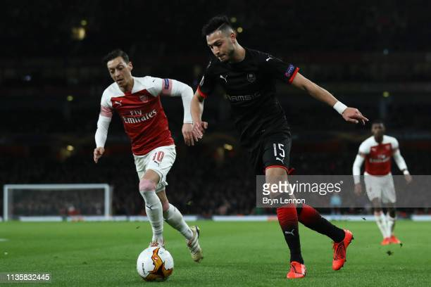 Ramy Bensebaini of Stade Rennais runs with the ball under pressure from Mesut Ozil of Arsenal during the UEFA Europa League Round of 16 Second Leg...
