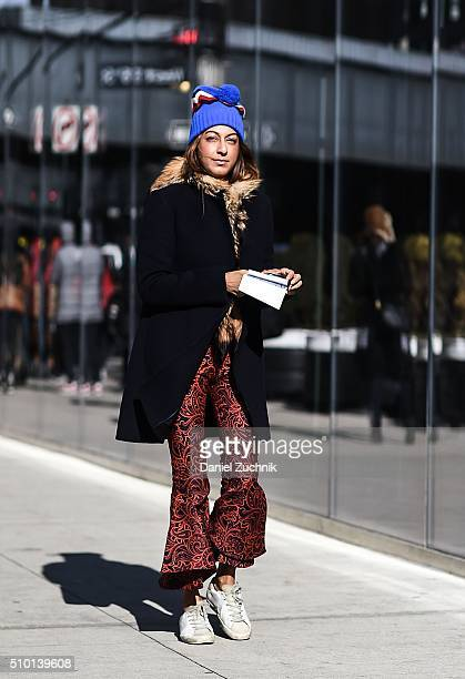 Ramya Giangola is seen outside the Tibi show wearing a Celine blue with fur trim coat and Golden Goose sneakers during New York Fashion Week Women's...