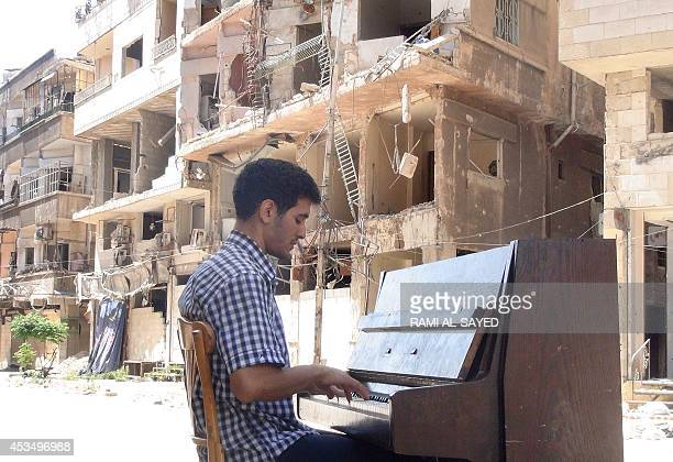 Rana Moussaoui Ayham alAhmed a resident of Damascus' Yarmuk Palestinian refugee camp plays the piano in the middle of the street near destroyed...