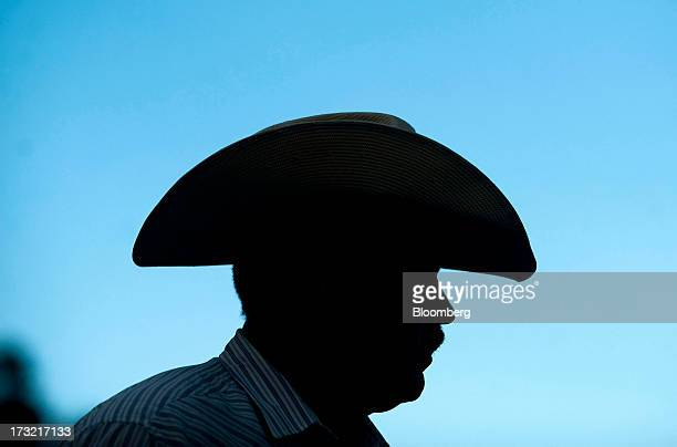 A ranch hand wearing a cowboy hat stands silhouetted at the Adams Ranch Inc in St Lucie County Florida US on Tuesday July 9 2013 Cattle futures for...