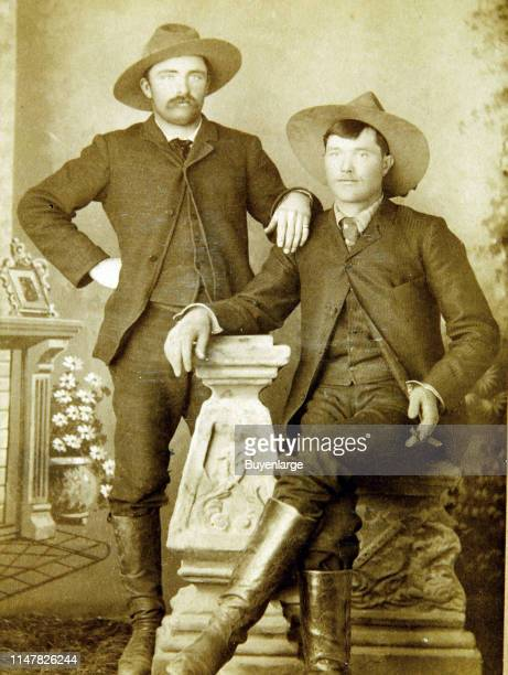 Ranch Hands Dressed In Matching Suits And Elegantly Posed In Front Of A Faux Setting That Includes A Mantle Flowers And Decorative Frame The Seated...