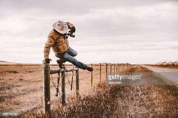 rancher jumps over barbed wire fence to get to road - wild west stock pictures, royalty-free photos & images