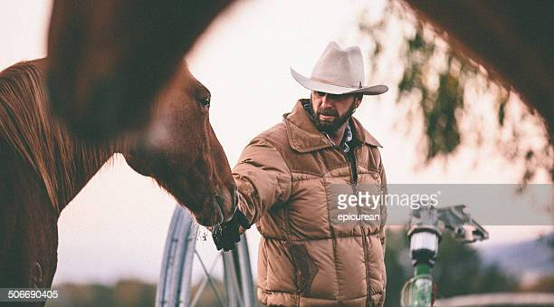 rancher pets horse on nose while working in field - rancher stock pictures, royalty-free photos & images