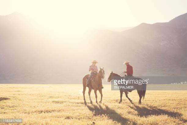 日の出に牧場カップル乗馬 - ウエスタン映画 ストックフォトと画像