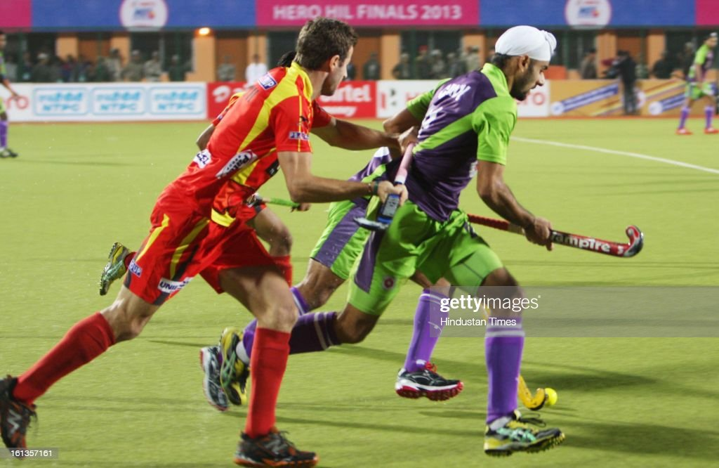 Ranchi Rhinos (red jersey) and Delhi Waveriders (violet and green jersey) teams in action during the Hockey India League (HIL) final match at Astro stadium on February 10, 2013 in Ranchi, India.