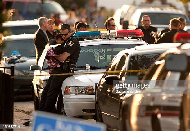 Rancho Cordova Sheriff holds a child that was unharmed in a triple homicide in a duplex in Rancho Cordova, California, on Tuesday, October 23, 2012....