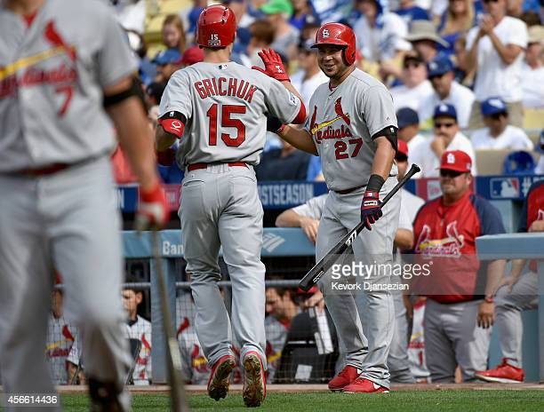Randal Grichuk of the St Louis Cardinals celebrates with teammate Jhonny Peralta after hitting a homerun to score in the first inning of Game One of...