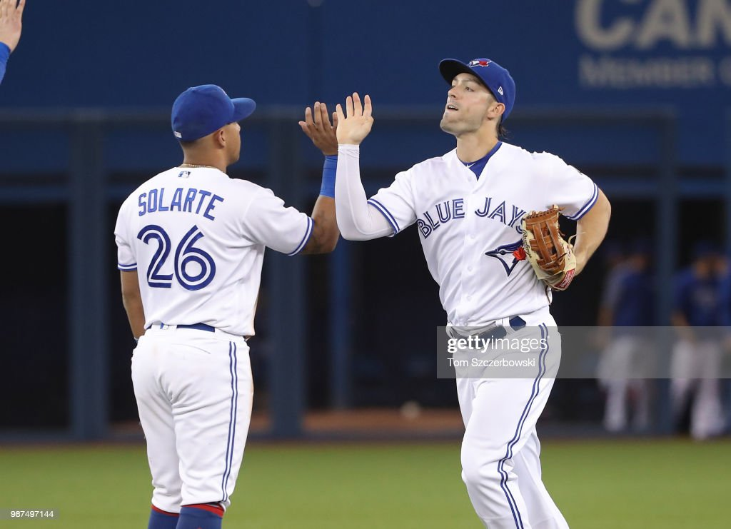 Randal Grichuk #15 of the Toronto Blue Jays celebrates their victory with Yangervis Solarte #26 during MLB game action against the Detroit Tigers at Rogers Centre on June 29, 2018 in Toronto, Canada.
