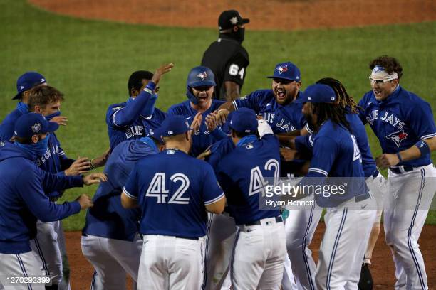 Randal Grichuk of the Toronto Blue Jays celebrates with teammates after hitting a walk-off two run home run during the tenth inning to beat the...