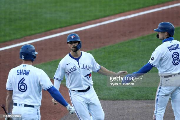 Randal Grichuk of the Toronto Blue Jays high-fives teammates Travis Shaw and Cavan Biggio after scoring during the first inning of a game against the...