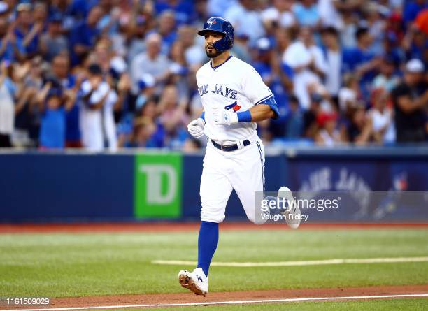 Randal Grichuk of the Toronto Blue Jays hits a solo home run in the second inning during a MLB game against the Texas Rangers at Rogers Centre on...