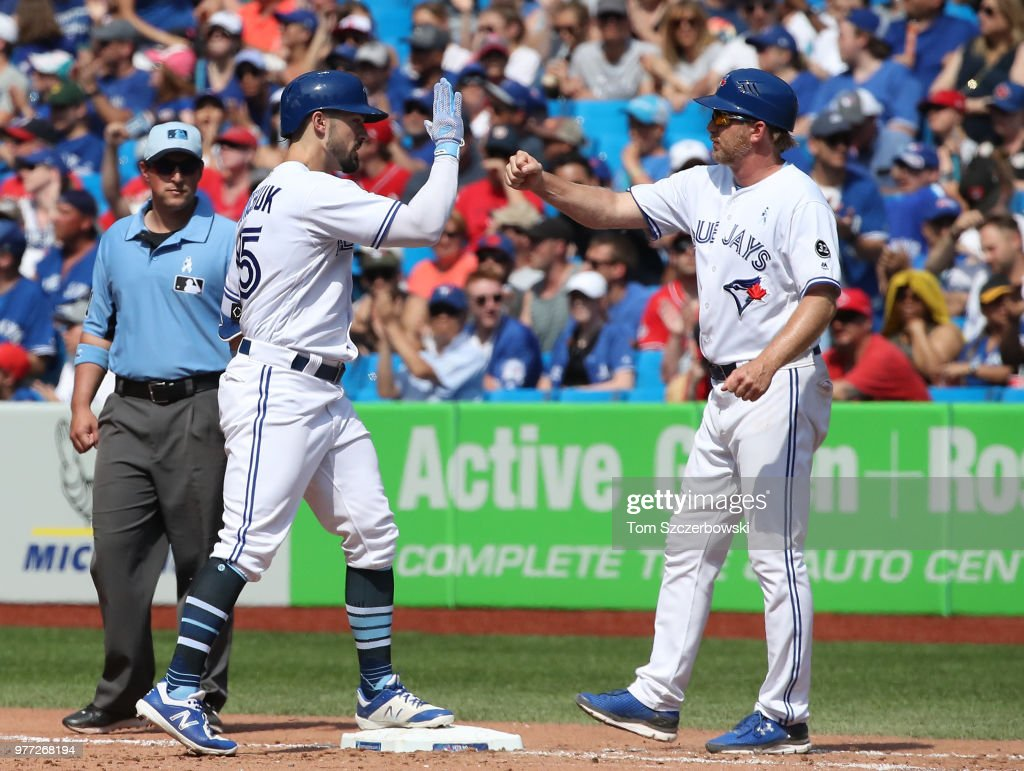 Randal Grichuk #15 of the Toronto Blue Jays is congratulated by first base coach Tim Leiper #34 after hitting an RBI single in the seventh inning during MLB game action against the Washington Nationals at Rogers Centre on June 17, 2018 in Toronto, Canada.