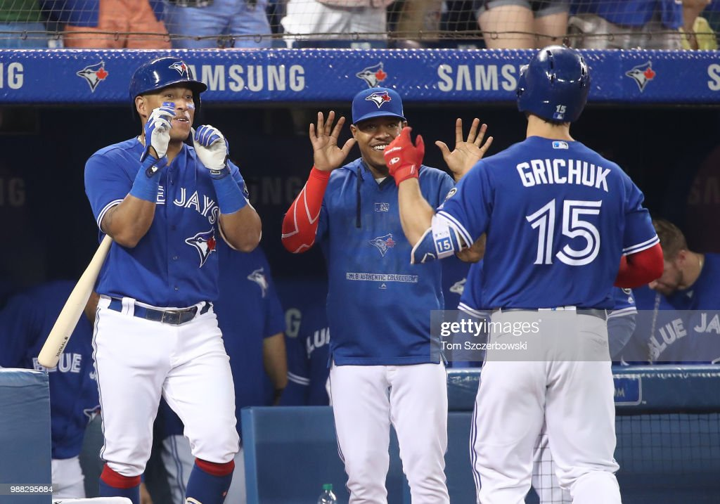 Randal Grichuk #15 of the Toronto Blue Jays is congratulated by Yangervis Solarte #26 and Marcus Stroman #6 after hitting a two-run home run in the fifth inning during MLB game action against the Detroit Tigers at Rogers Centre on June 30, 2018 in Toronto, Canada.