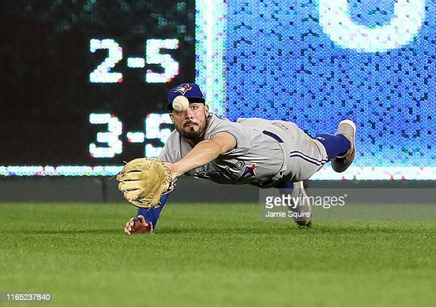 Randal Grichuk of the Toronto Blue Jays makes a diving catch during the 8th inning of the game against the Kansas City Royals at Kauffman Stadium on...