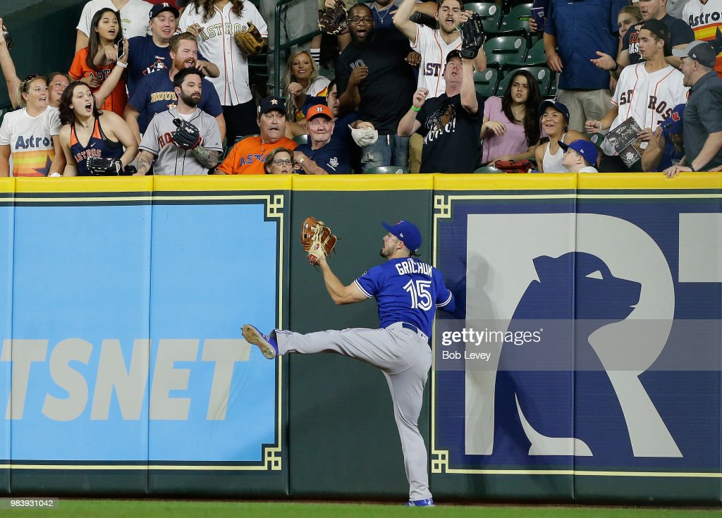 Randal Grichuk #15 of the Toronto Blue Jays makes a leaping catch at the wall to take away a three run home run from George Springer #4 of the Houston Astros in the ninth inning at Minute Maid Park on June 25, 2018 in Houston, Texas.