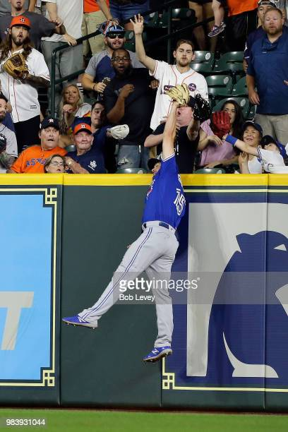 Randal Grichuk of the Toronto Blue Jays makes a leaping catch at the wall to take away a three run home run from George Springer of the Houston...