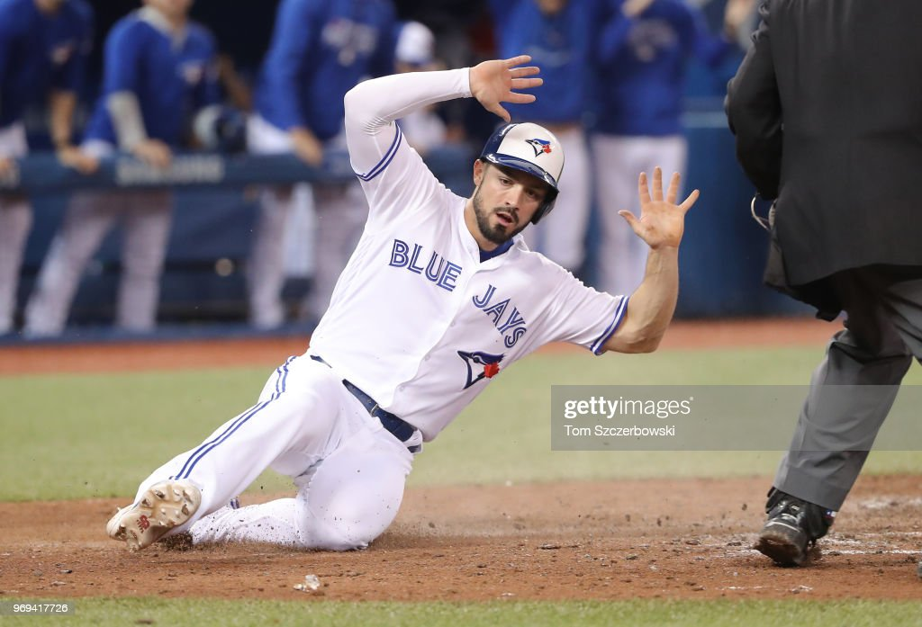 Randal Grichuk #15 of the Toronto Blue Jays reacts as he slides safely across home plate to score the tying run in the ninth inning during MLB game action against the Baltimore Orioles at Rogers Centre on June 7, 2018 in Toronto, Canada.