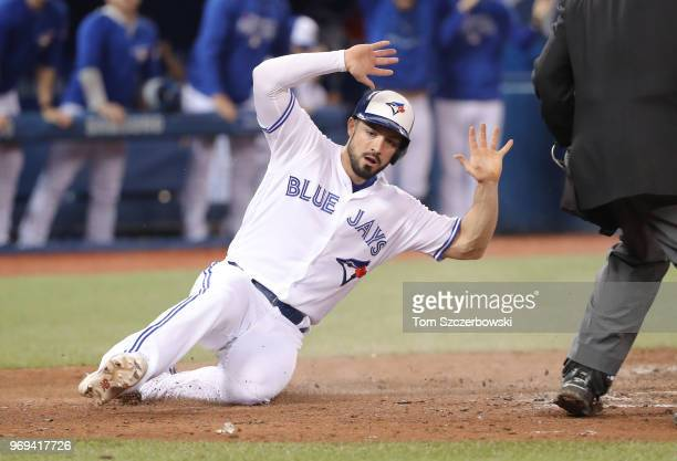 Randal Grichuk of the Toronto Blue Jays reacts as he slides safely across home plate to score the tying run in the ninth inning during MLB game...