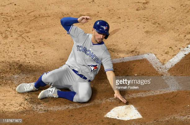 Randal Grichuk of the Toronto Blue Jays slides safely into home plate to score a run against the Minnesota Twins during the seventh inning of the...