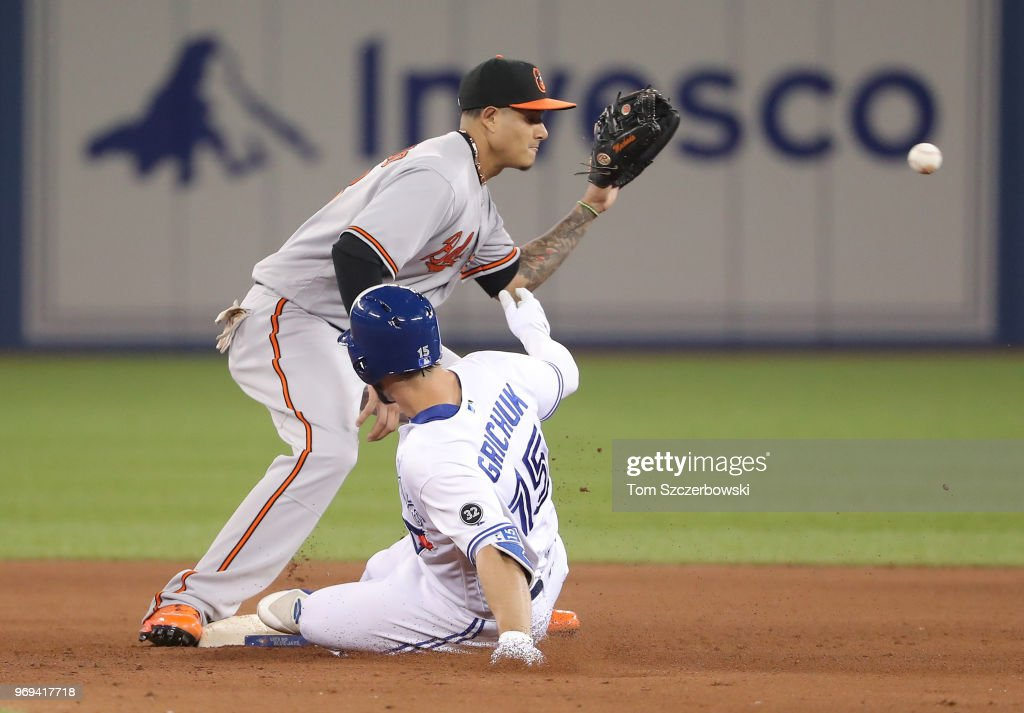 Randal Grichuk #15 of the Toronto Blue Jays slides safely into second base with a two-run double in the ninth inning during MLB game action as Manny Machado #13 of the Baltimore Orioles waits for the throw at Rogers Centre on June 7, 2018 in Toronto, Canada.