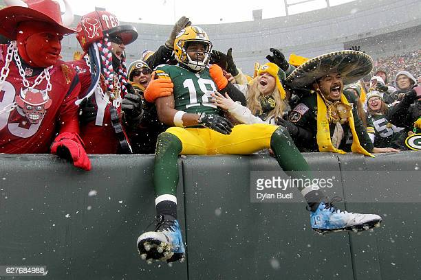 Randall Cobb of the Green Bay Packers celebrates with fans with a 'Lambeau Leap' after scoring a touchdown in the second quarter against the Houston...
