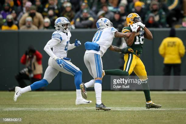 Randall Cobb of the Green Bay Packers makes a catch while being guarded by Tracy Walker and Teez Tabor of the Detroit Lions in the third quarter at...
