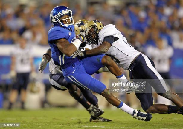 Randall Cobb of the Kentucky Wildcats is tackled by Doug Richardson of the Akron Zips during the game at Commonwealth Stadium on September 18 2010 in...