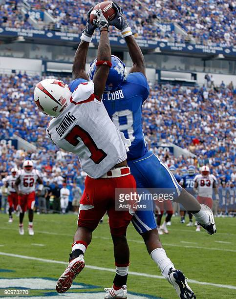 Randall Cobb of the Kentucky Wildcats reaches for the game winning touchdown while defended by Karldell Dunning of the Louisville Cardinals during...