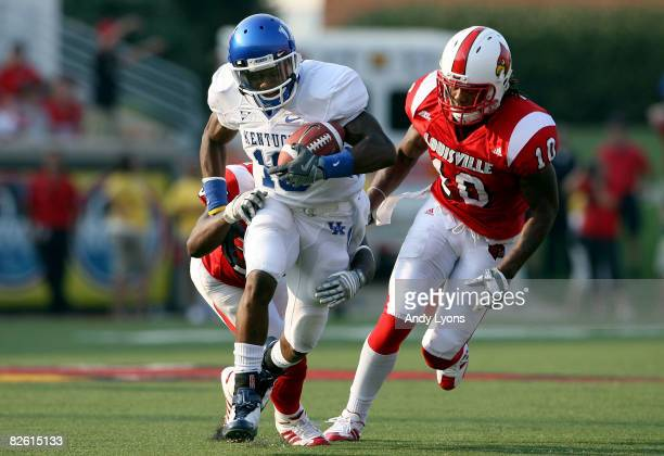 Randall Cobb of the Kentucky Wildcats runs with the balll while defended by Bobby Buchanan and Latarrius Thomas of the Louisville Cardinals during...