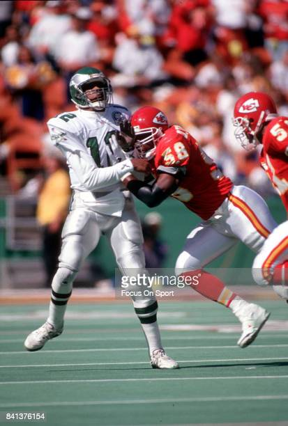 Randall Cunningham of the Philadelphia Eagles throws a pass under pressure from Derrick Thomas of the Kansas City Chiefs during an NFL Football game...