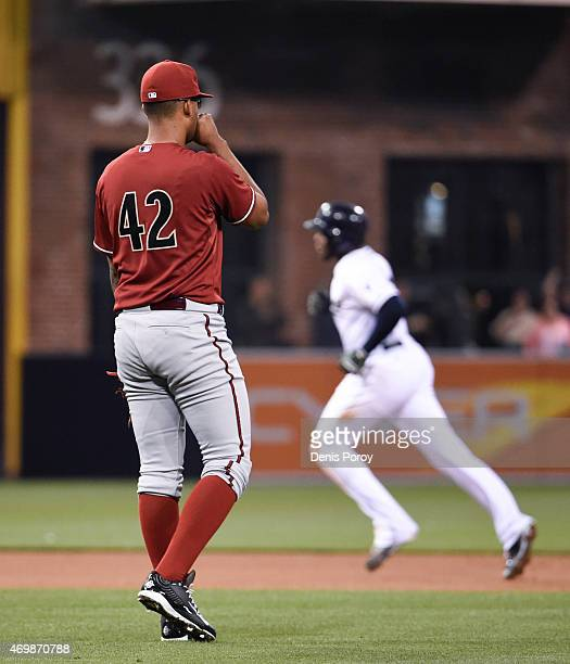 Randall Delgado of the Arizona Diamondbacks looks to the outfield as Justin Upton of the San Diego Padres rounds the bases after hitting a solo home...