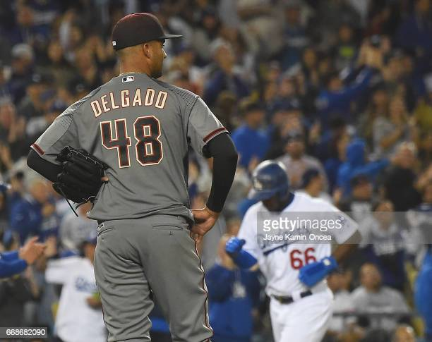 Randall Delgado of the Arizona Diamondbacks stands on the mound as Yasiel Puig of the Los Angeles Dodgers rounds the bases to score on a two run home...